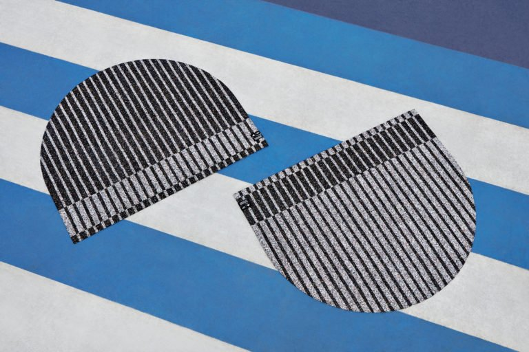 Black and white Adidas stripped rugs on a sport court by designer Simone Post.